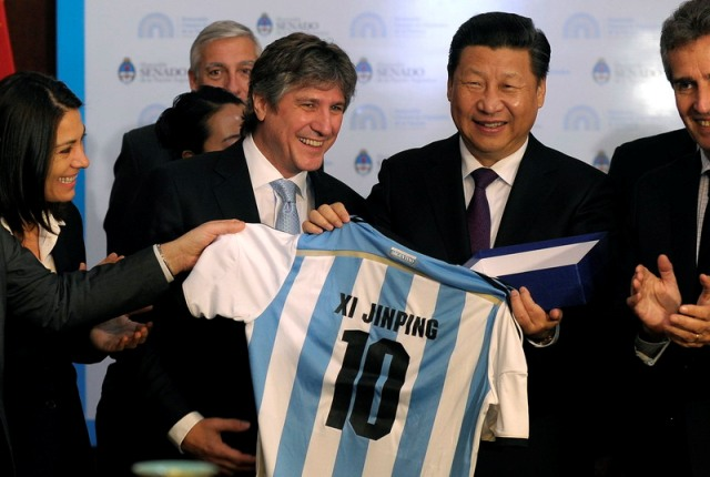 In this photo provided by Argentina's Senate Argentina's Vice President Amado Boudou, left, gives an Argentina's T-shirt to China's President Xi Jinping, right, at the National Congress in Buenos Aires, Argentina, Saturday, July 19, 2014. (AP Photo/Alejandro Pagni/Senate Press)